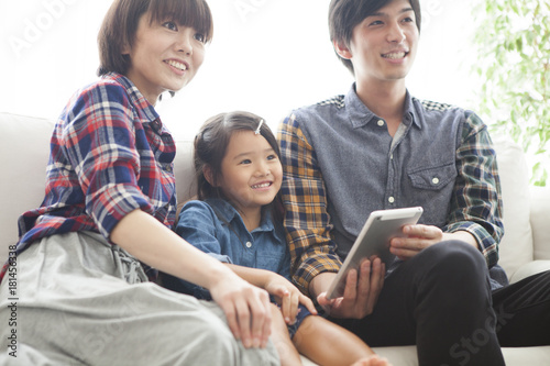 Parents and daughter are sitting on the sofa and using a digital tablet together.