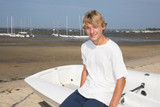 Handsome young man happy tanned, blond with boat on the beach - 181461390