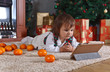 Little girl with tablet in the room with Christmas decorations