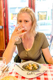 Female drinking wine glass eating snails with herbs butter. Traditional French dish: escargots de Bourgogne. Tourist woman in typical local street food in Paris.Lifestyle woman in restaurant for lunch - 181465192