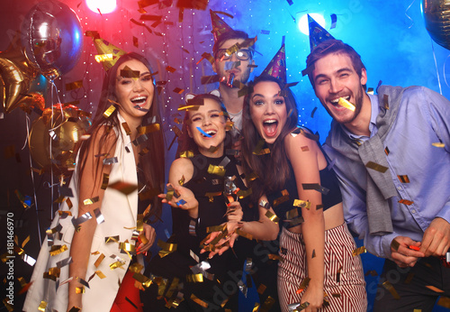 Cheerful young people showered with confetti on a club party. - 181466970
