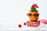 Closeup of pineapple in sunglasses and red hat with christmas decorations over white background. Copy space. Christmas in exotic country concept. - 181467781
