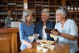Senior female friends using digital tablet while having drinks - 181468142