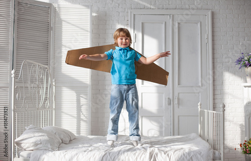 Happy boy with cardboard boxes of wings in home dream of flying Poster