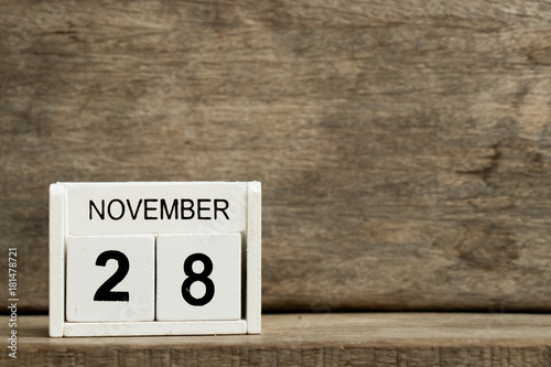 Poster White block calendar present date 28 and month November on wood background