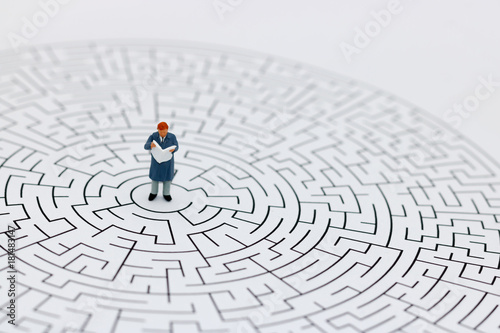 Miniature people: Businessman reading on center of maze  Concepts of