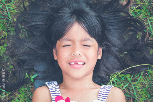 Toothless Little girl closing her eyes  sleeping on the grass in the park Poster