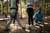 Kids walking on rope bridge in park