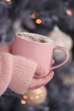 Hands of the girl in a fluffy soft sweater close-up with a cup of fragrant coffee with foam against the backdrop of sparkling lights of a Christmas tree, a Christmas tree.