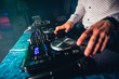 DJ plays music at night club at party by controlling the buttons and levels