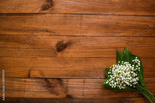 Fotobehang Lelietjes van dalen Lilies of the valley on a wooden old background and free space for your text.