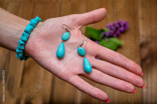 Bracelet and earrings of turquoise on a woman's palm.