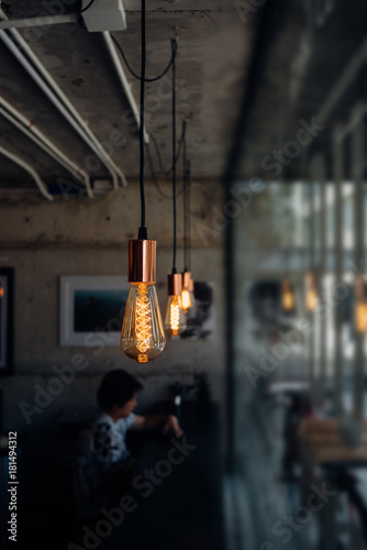 Incandescent light bulb and woman in coffee shop Poster