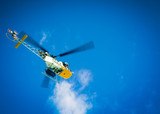 Yellow helicopter against blue sky and clouds trailing a haul line