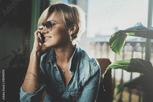 Portrait smiling young woman wearing casual clothes and talking on smartphone device while spending relax time in vacation travel.Attractive woman owner communicating on cellular.Blurred background.