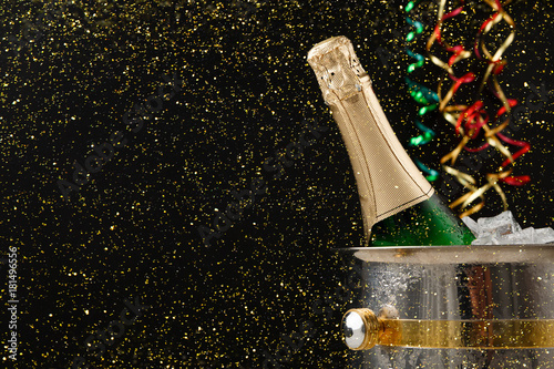 Bottle of champagne in a bucket on dark backgroud. Copy space Poster