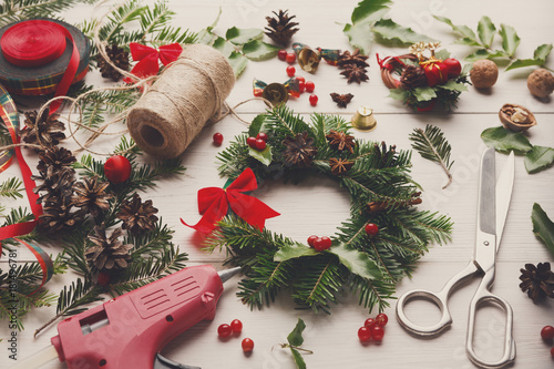 Prepare for xmas. Handmade craft wreath. Making christmas decoration. Tolls, wreath white desk