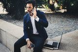 Elegant young businessman working outside with mobile laptop pro. Handsome man using modern smartphone for call.Blurred background.Horizontal.