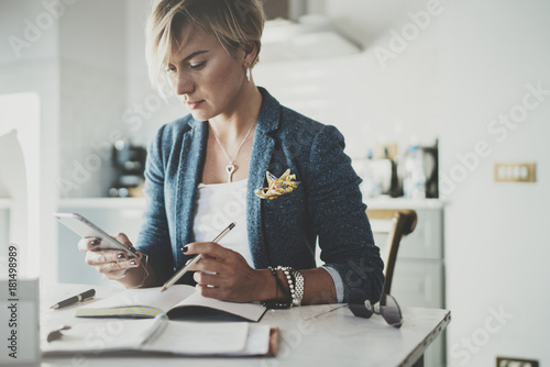 Attractive businesswoman texting sms with partner via modern telephone while writing some information in note book while sitting at living room in hotel.Blurred background.