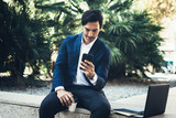 Attractive smiling businessman making video conversation with partners by mobile phone.Man using contemporary smartphone sitting outside.Blurred background. Horizontal.
