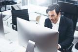 Elegant man using desktop computer at modern office.Panoramic windows on blurred background.Horizontal.
