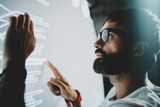 Concept of virtual panel display,diagram,digital graph interfaces.Young bearded man touching virtual panel with graphs.Blurred background. Horizontal.