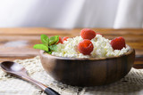 Cottage cheese with fresh raspberry in a wooden bowl on old wooden background with copy space for your text. Top view - 181501114