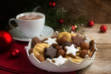christmas cookies and a coffee cup with hot cocoa, fir tree branches and red baubles on rustic wood, cozy advent afternoon, copy space - 181503589