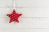 star of red patterned fabric hanging on a rustic white painted wooden wall, christmas background with large copy space - 181503743