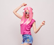 DJ Girl Hipster with Pink Fashion Hairstyle Dance. Young Playful Model Woman in Trendy Headphones Smiling. DJ Music vibrations, Clubbing. Party Style