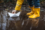 Child with Yellow Rain Boots and a little White Paper boat / Ship: Playing in a puddle, imagining his adventures - 181505303