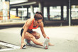 Female runner stretching and relaxing on  city street after jogging. - 181506793