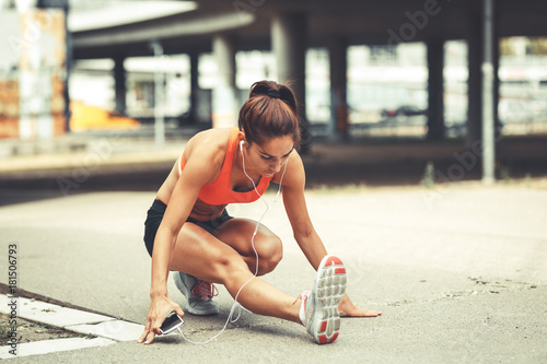 Aluminium Hardlopen Female runner stretching and relaxing on city street after jogging.