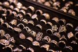 Many different silver rings on black velvet