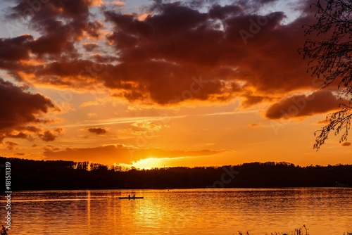 Foto op Canvas Rood paars Ruderer bei Sonnenuntergang am See