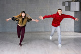 Guy and girl in dance movement. Modern style young dancers performing hip-hop dance on studio background. Teenagers skill and talent of modern dance. - 181511980