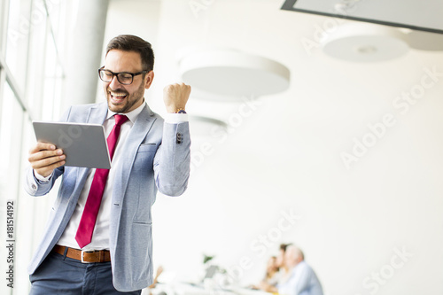Fototapeta Happy businessman with tablet in office