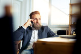 Portrait of businessman talking on mobile phone in office - 181514955