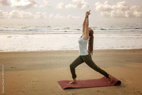 Junge Frau meditiert beim Yoga am Strand
