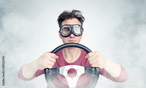 Man in stylish goggles with steering wheel on background, car driver concept