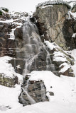 Waterfall in mountains at winter