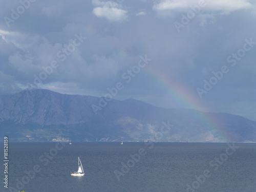 Yacht under a rainbow in front of a mountain Poster