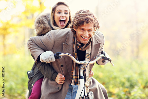 Happy couple on bikes in forest during fall time Poster