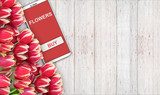 background of buying and selling flowers, red tulips on the table and the phone.