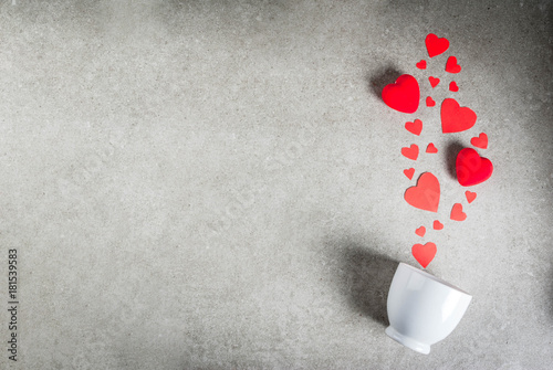 Fotobehang Chocolade Romantic background, Valentine's day. A gray stone table with a cup for coffee or hot chocolate, decorated with paper and plush red hearts, top view flat lay, copy space