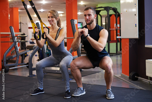 Slim woman with personal trainer working with battle ropes at gym