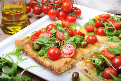 Papiers peints Pizzeria Focaccia with cherry tomatoes, arugula, olives and extra virgin olive oil