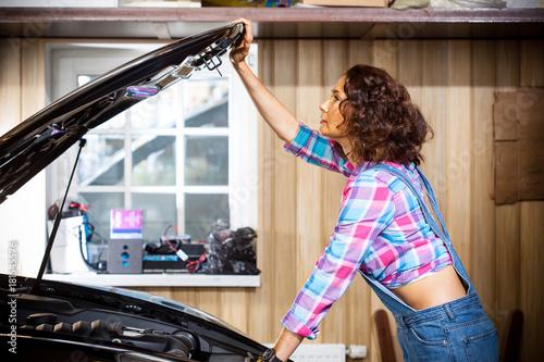 beautiful woman mechanic in a garage Plakát