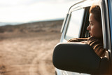 Woman looking out the window of her car - 181550728