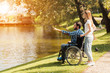 A woman is walking in the park with a man in a wheelchair. They are on the shore of a lake.